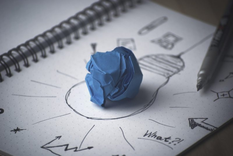 Image showing a crumpled piece of paper on a drawing of a lightbuld to represent innovation